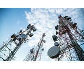 Mobilfunkmasten vor blauem Himmel mit Woken