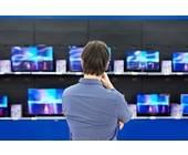 Mann steht vor Verkaufsregal mit Fernsehern