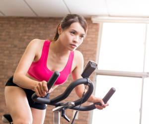 Frau trainiert auf Fahrrad-Heimtrainer