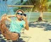 Urlauber mit Smartphone in Hängematte