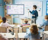 Lehrer zeigt auf Whiteboard