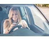 Autofahrerin mit Handy im Auto