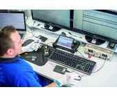 Mann sitzt vor Computer und repariert ein Smartphone