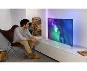 Mann sitzt vor Philips-Fernseher