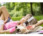 Frau liegt auf einer Wiese und hört Musik