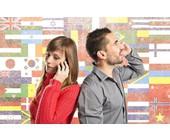 Frau und Mann telefonieren mit einem Smartphone vor einer Wand mit Landesflaggen