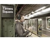 Mann steht mit Kopfhörer auf dem Kopf in einer Ubahnhaltestelle