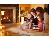 Famile vor Kamin mit Tablet