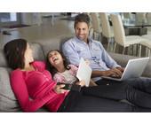 Familie sitzt auf der Couch mit mobilen Geräten