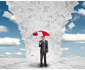 Mann mit Regenschirm schützt sich vor Papier