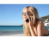 Frau mit Handy am Strand