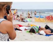 Frau am Strand mit Smartphone
