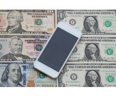 Smartphone liegt auf Dollar-Noten